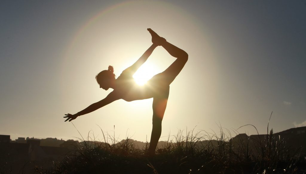 Silhouette of acrobatic teen gymnast balancing with the sun behind her