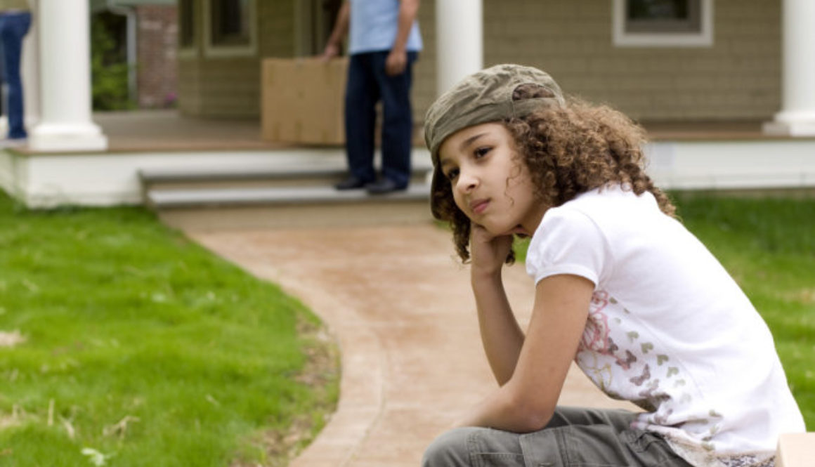 Upset girl sitting on moving boxes outside house