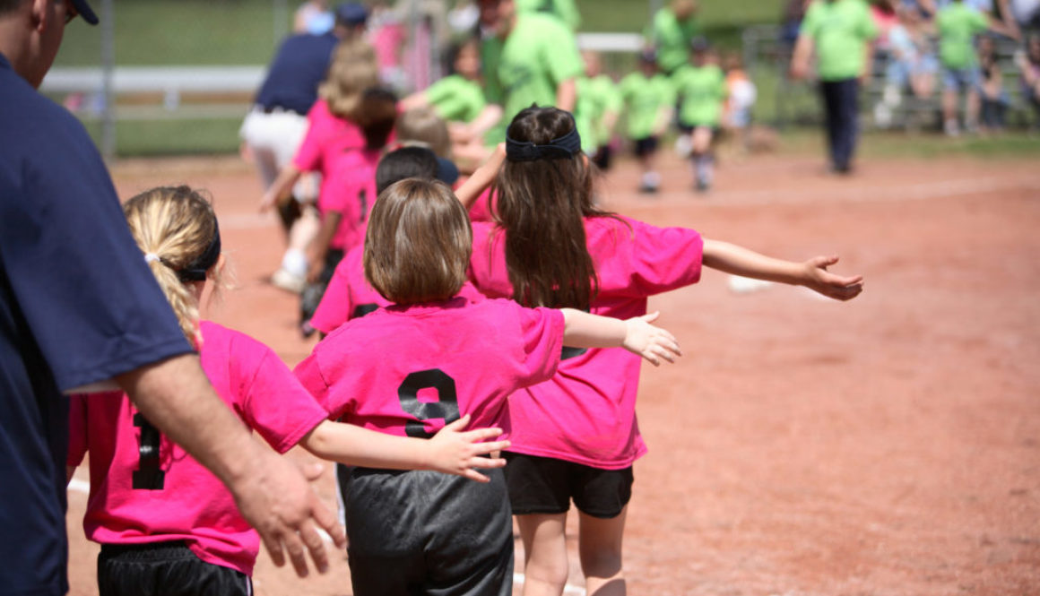 Young girls in pink and black sports gear playing outside