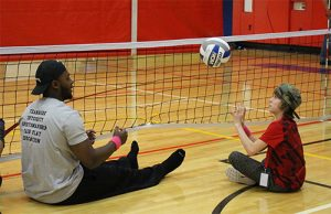 An adult mentor and youth practice sitting volleyball at the 2017 Playmakers Program.