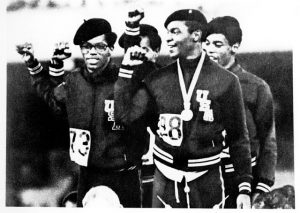 Photo of Olympians Ron Freeman, Lee Evans, Larry James, and Vincent Matthews in black berets holding up fists.