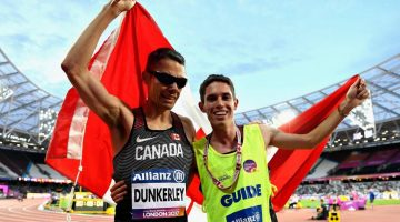 Two men holding Canadian flag after finishing a race.