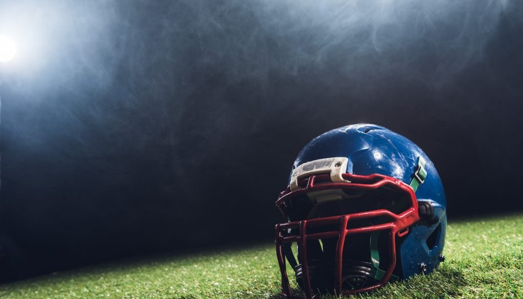 close-up shot of american football helmet on green grass with white smoke above