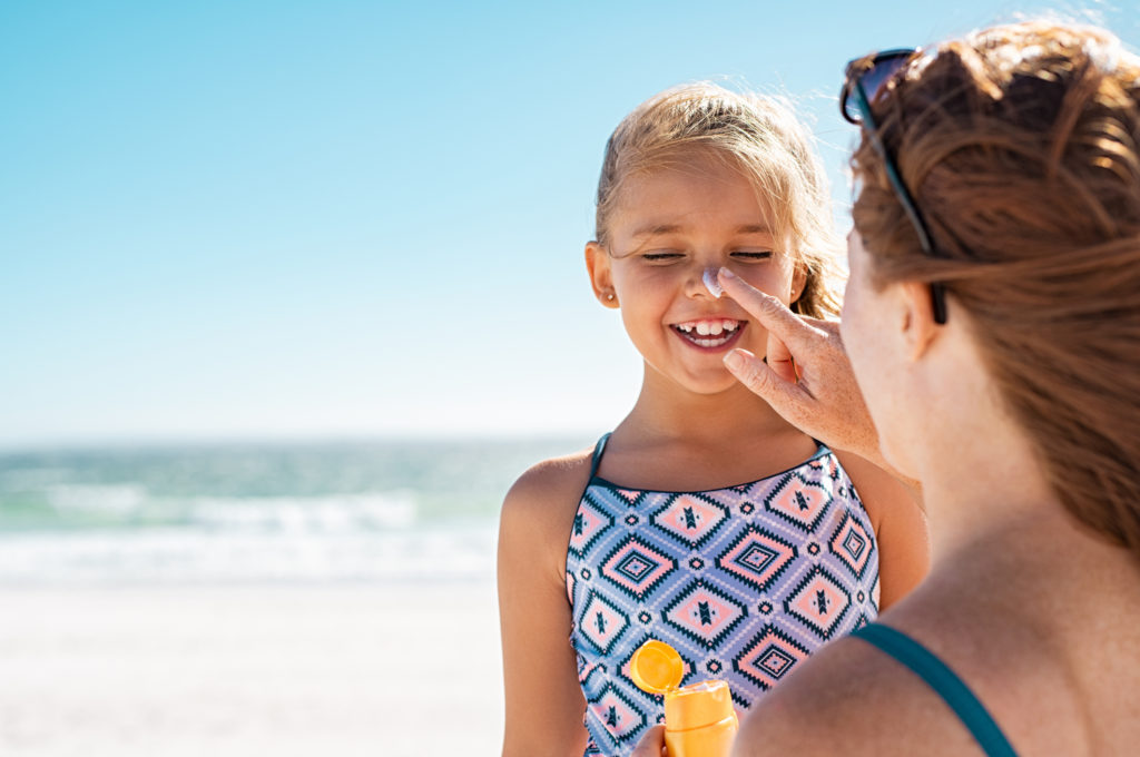 mother applying sunscreen to little girl