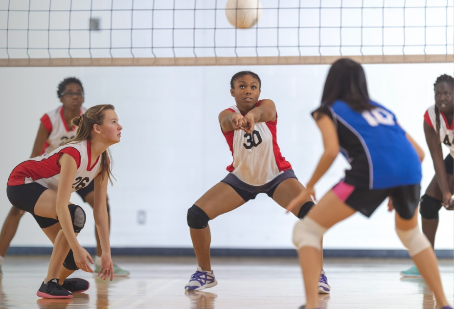 teenage girl poised to bump a volleyball next to teammates
