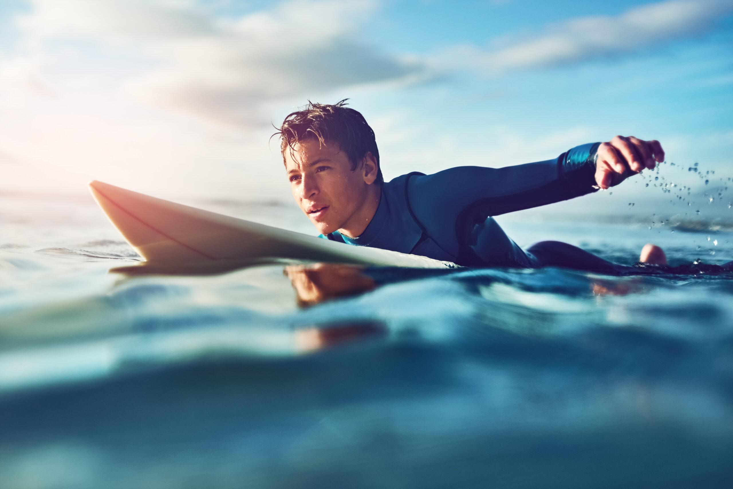 teen boy on surfboard in water