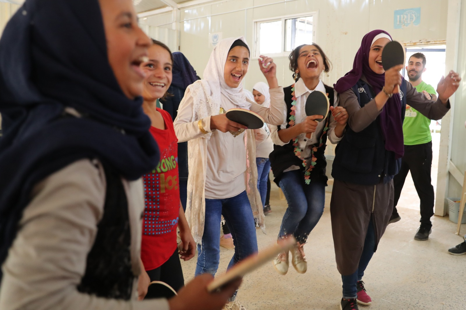 Young women in the Zaatari Refugee Camp in Jordan smile and hold table tennis paddles.