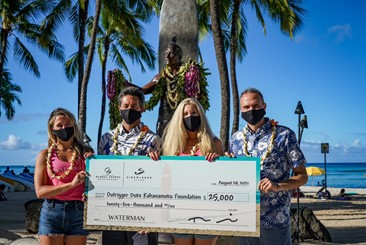Two women and two men wearing face masks on the beach hold a large check